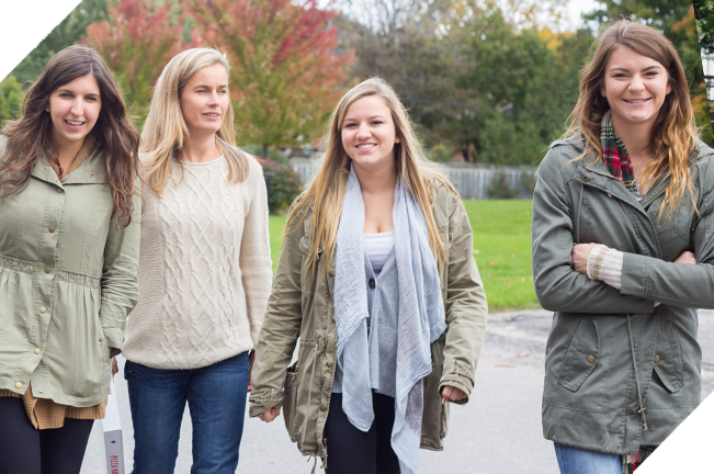 Four young women walking side by side