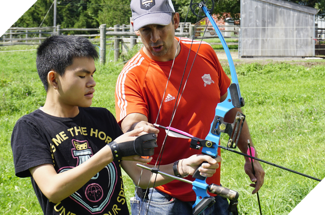 Male staff guiding a youth in archery