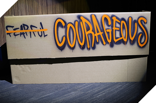"""Graffiti art of the word """"fearful"""" crossed out and the word """"courageous"""" bolded in orange"""