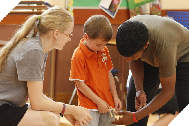 Male and female camp leaders helping a young boy with a craft