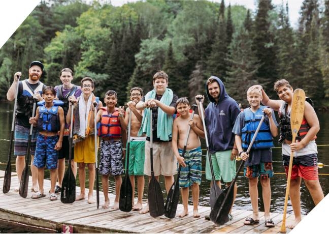 Group of young men wearing life jackets and holding canoeing oars