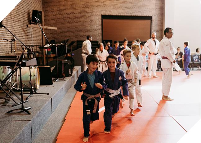 Two young boys running in jiu jitsu class