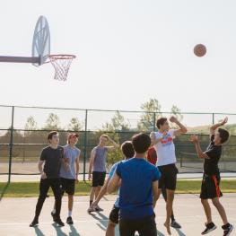 Group of boys playing basketball outdoors