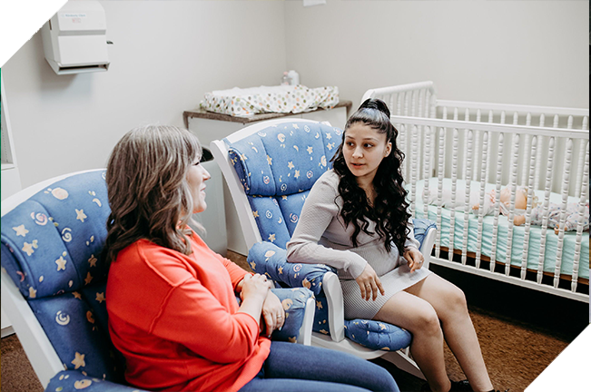 Two women conversing while sitting in rocking chairs in a baby's room