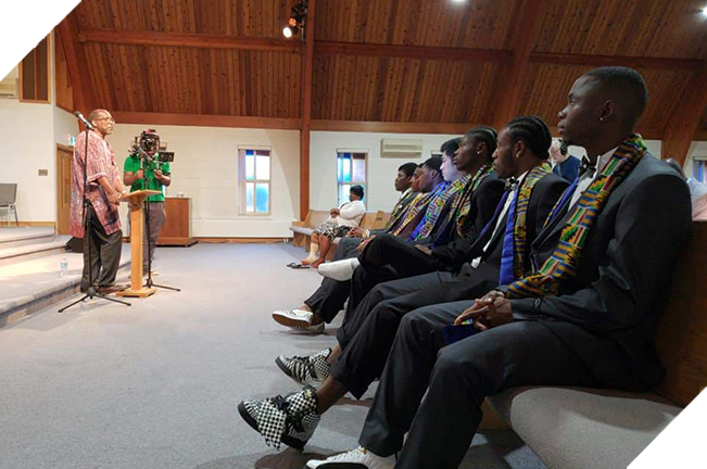 Pastor speaking and church members in front row seats during service