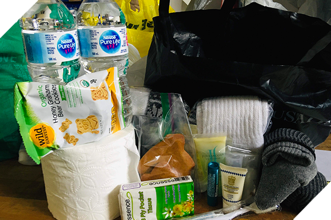 Care package with water, snacks, socks, tissues and toiletries