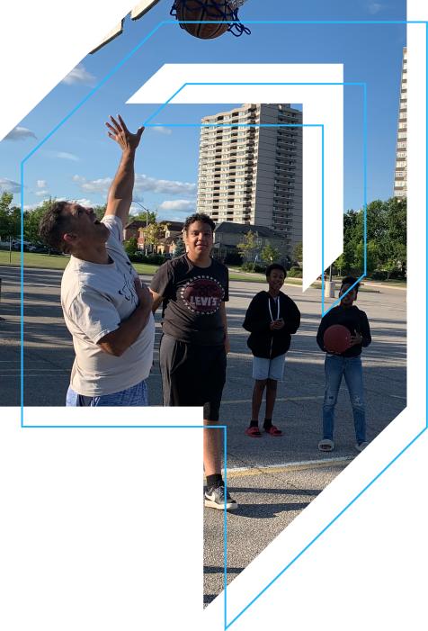 Four people playing basketball outdoors