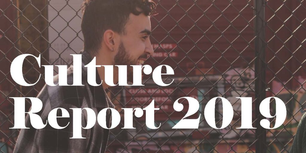 """Man standing in front of wired fence with text saying """"Culture Report 2019"""""""