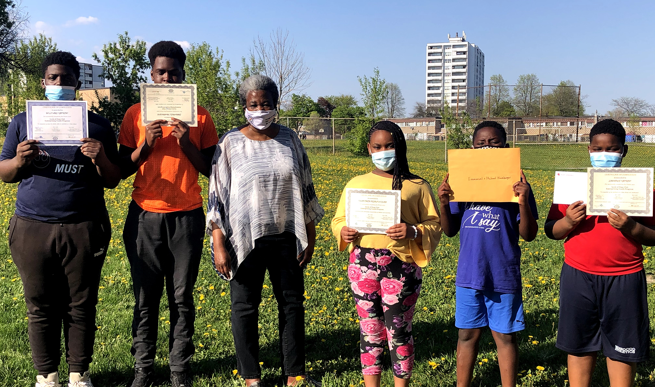 Jane and Finch outreach worker standing alongside 5 youth holding their program certificates