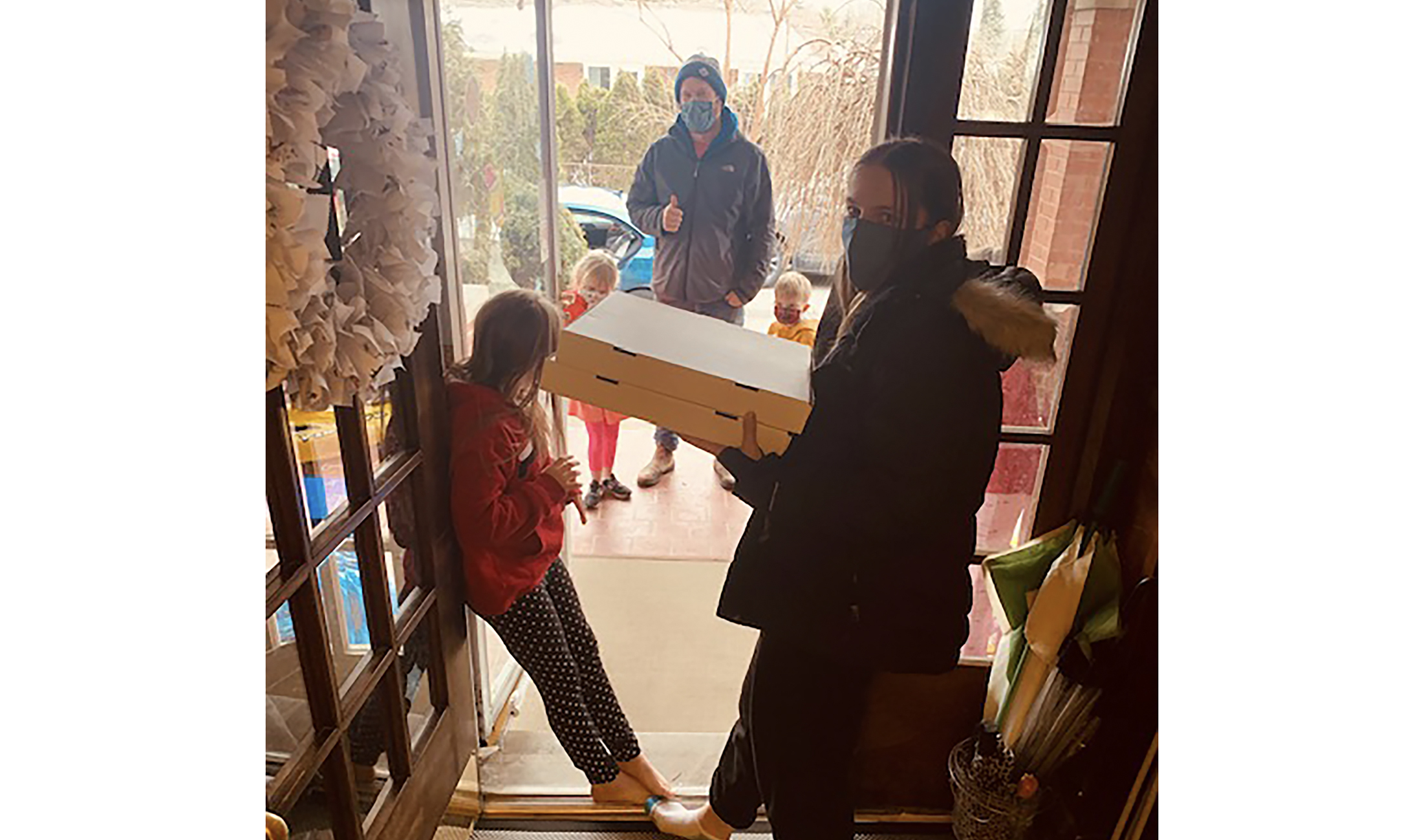 Two young people at their front door receiving pizza delivery from YU staff