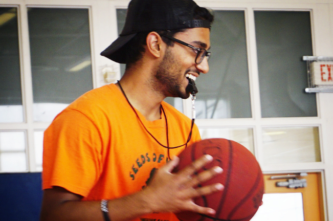 Young man a blowing whistle and holding a basketball