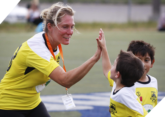 Female soccer leader high-fiving young player