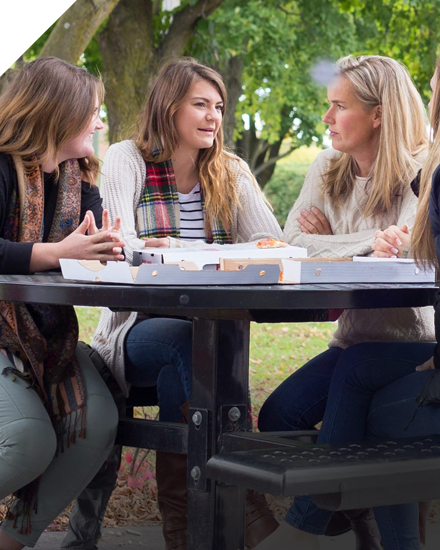 Three women sitting at a table conversing outdoors