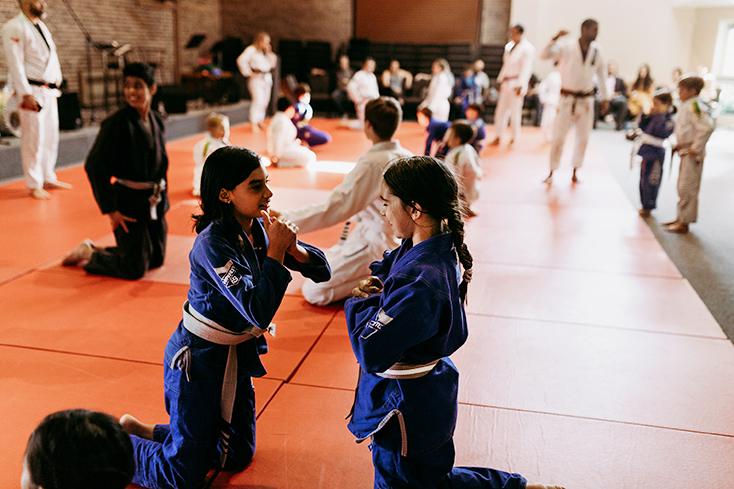 Two young girls kneeling on a mat in a busy jiu jitsu class