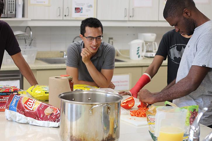 Four men in a kitchen preparing meals