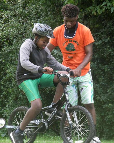 Male volunteer teaching young boy to ride a bike